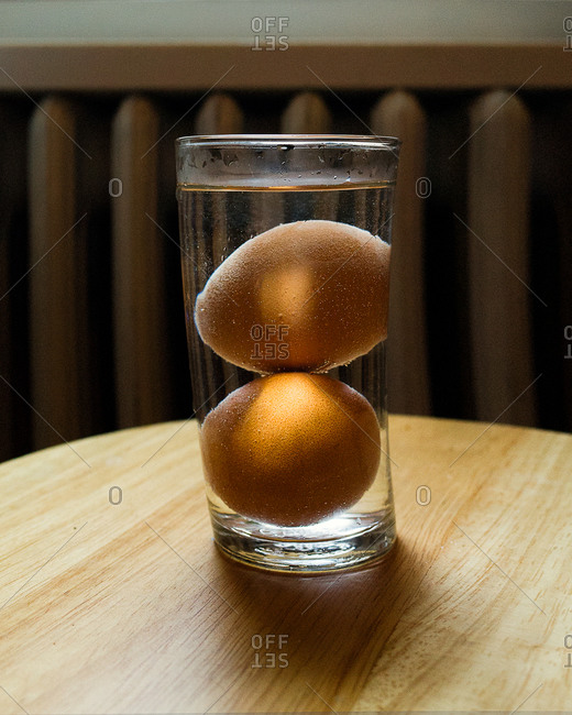 Two eggs submerged inside a glass cup
