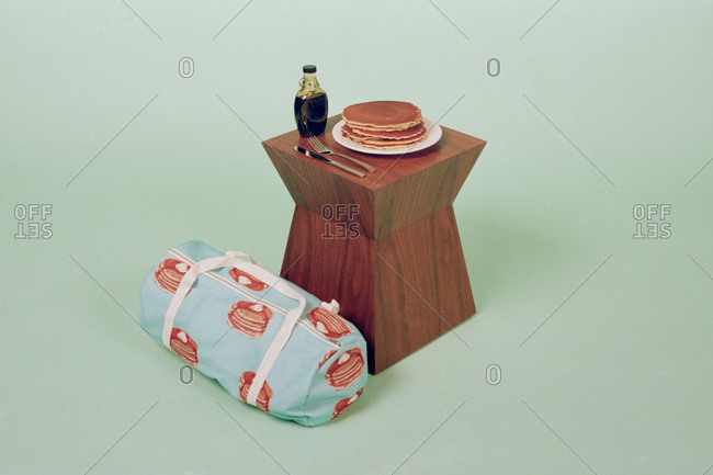 A plate of pancakes next to a duffle bag with a pancake print