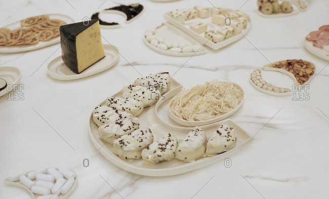 A variety of food served on curved plates on a marble surface