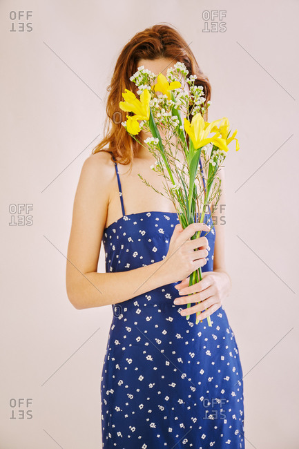 Woman covering her face with yellow and white flowers