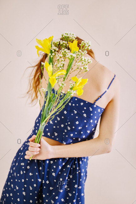 Young female holding flowers behind back
