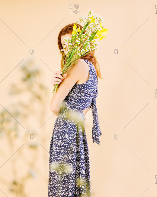 Young woman holding flowers crossing her arms