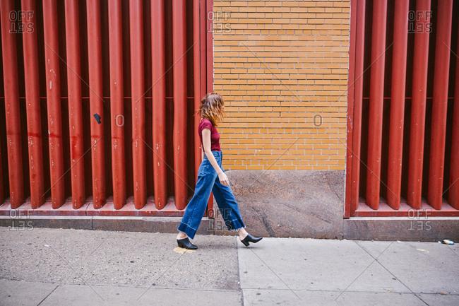 Young woman walking on sidewalk