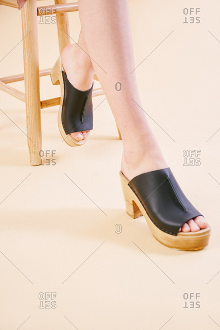 Close up of woman siting a stool wearing clogs