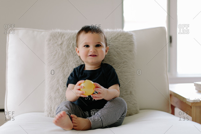 Cute baby boy with ball on white cushioned chair