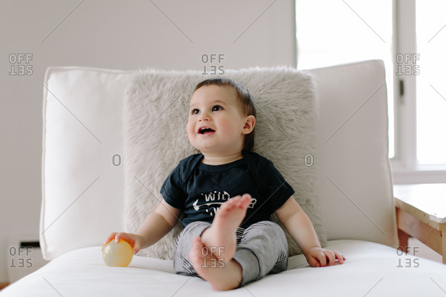 Portrait of a happy baby boy with ball on chair