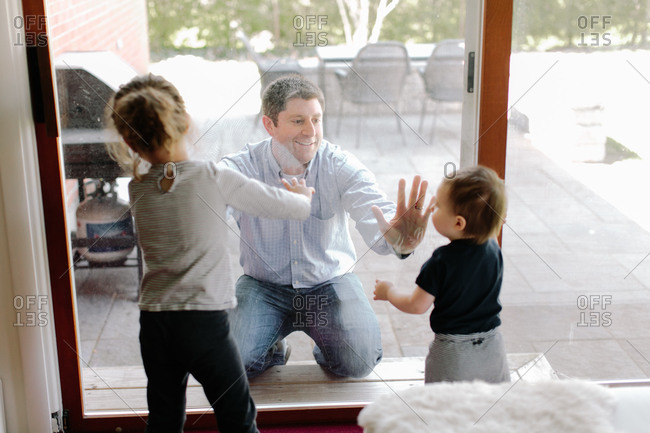 Two young children play with father on opposite sides of sliding door
