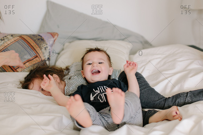 Two young siblings rolling playfully on bed
