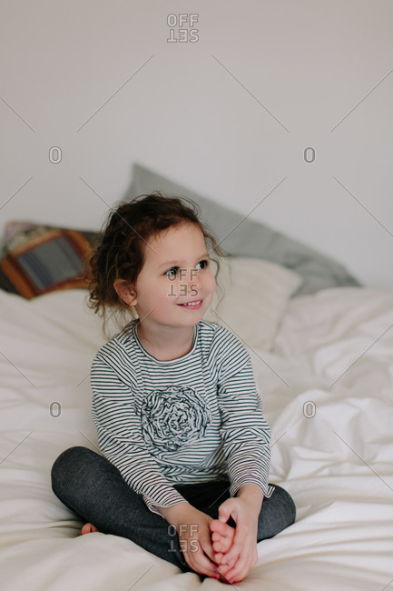 Portrait of a young girl with brown hair and brown eyes sitting on bed