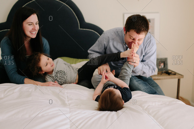 Parents play with their two young children on bed
