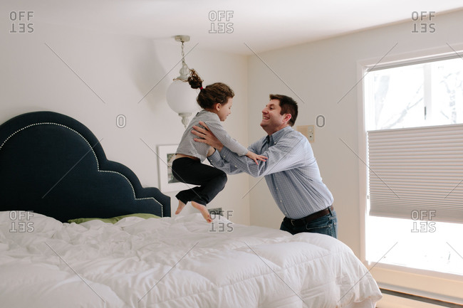 Young girl jumping on bed into arms of her father