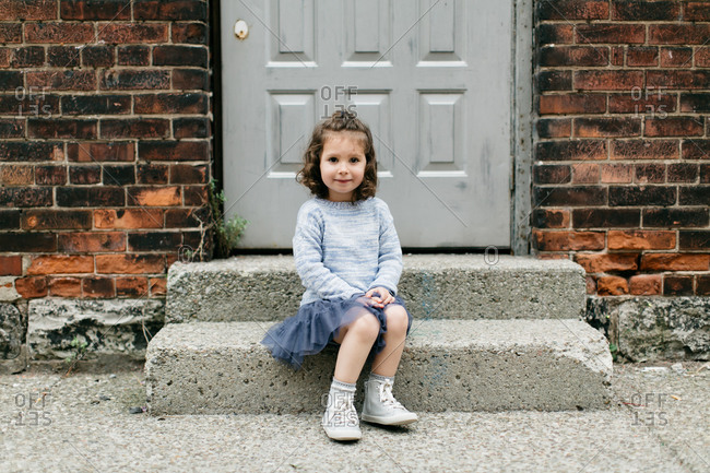 Portrait of a young girl sitting on steps of brick building on city sidewalk