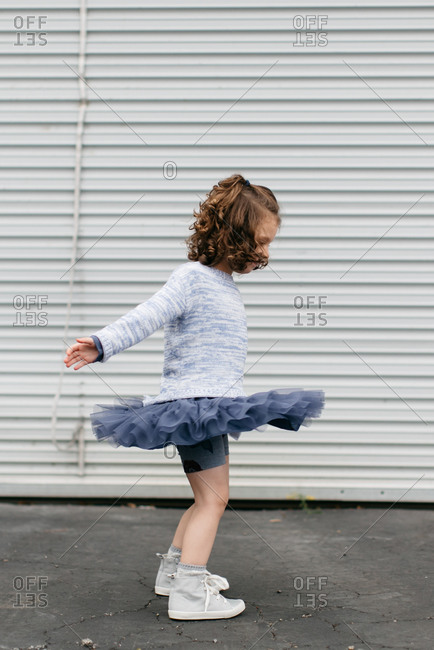 Young girl spinning skirt around on sidewalk