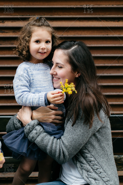 Mother hugging young daughter as she stands on bench