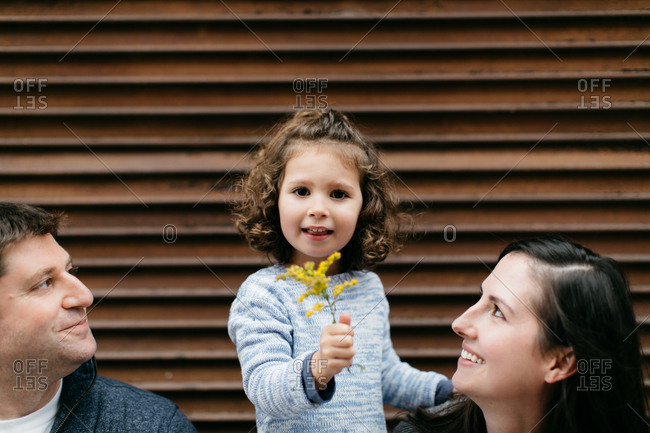 Mother and father gaze adoringly at their young daughter