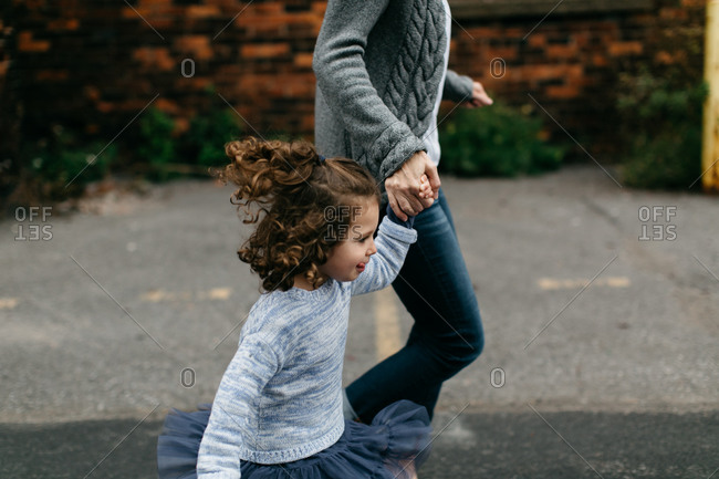 Young girl running alongside mother on sidewalk