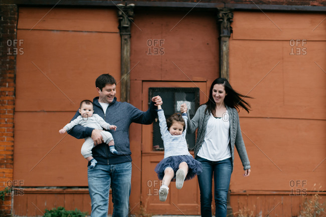 Family of four swing their young daughter by her arms