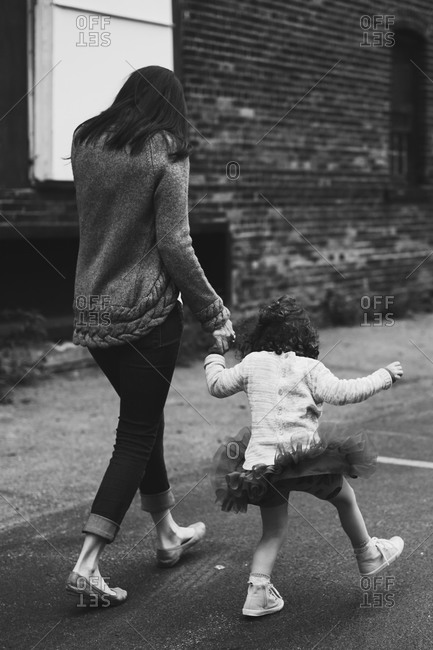 Mother walking hand in hand with playful young daughter
