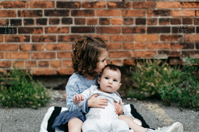 Young girl kissing her infant brother in front of brick building