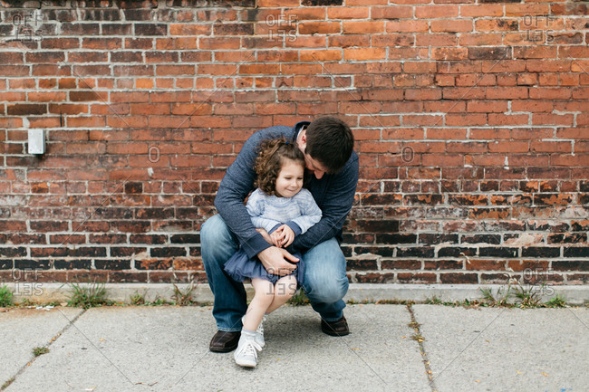 Father hugs his playful young daughter on sidewalk