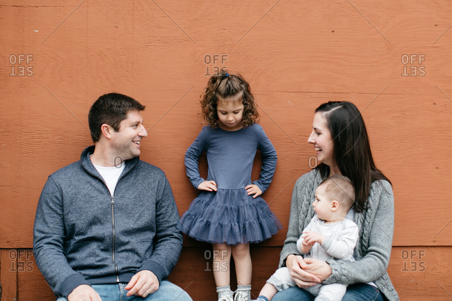 Parents gaze at young daughter standing between them