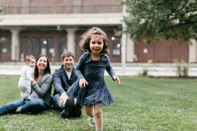 Young girl runs in park as parents watch