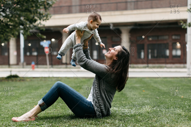 Woman plays with baby boy in park