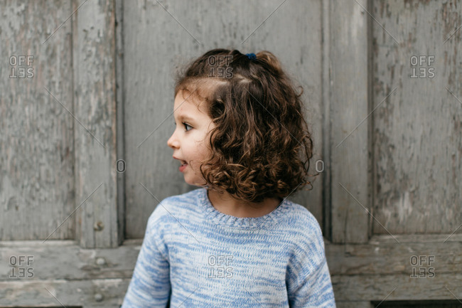 Portrait of young girl with her head turned in profile against a gray wooden door