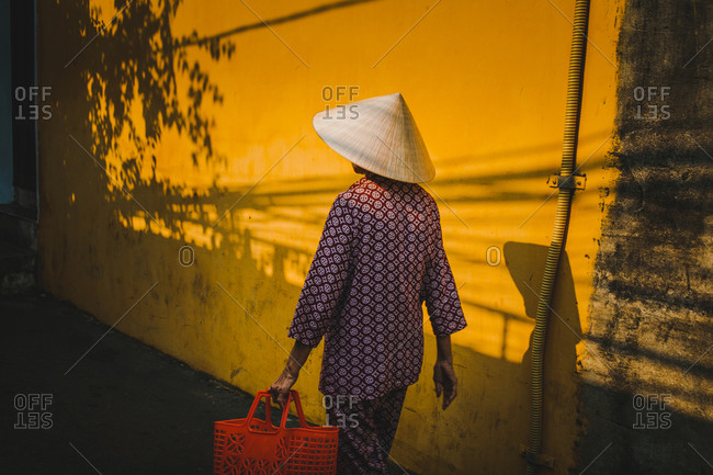 Woman wearing conical hat walking down the street in Hoi An, Vietnam