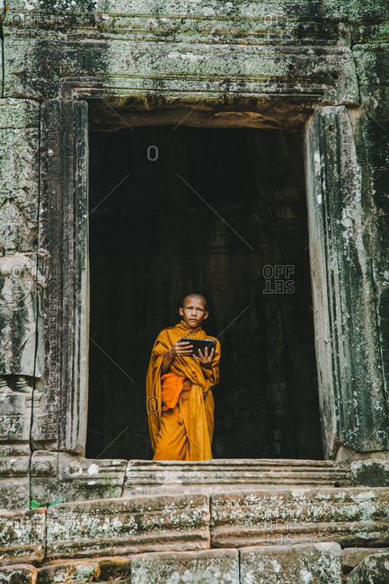Angkor Wat, Cambodia 4/9/2016: Young monk standing in ruins with a tablet in Angkor Wat, Cambodia.