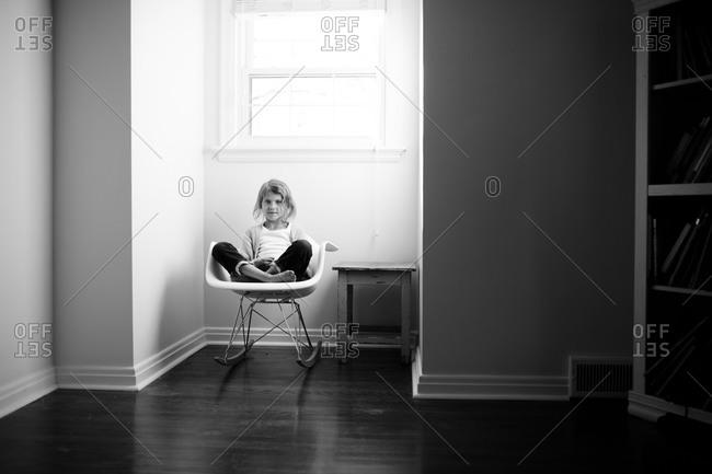 Girl in rocking chair in bedroom