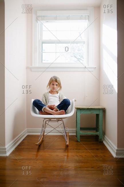 Girl in rocking chair in window