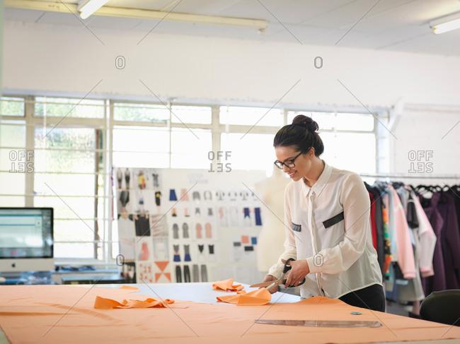 Fashion designer cutting cloth in fashion design studio