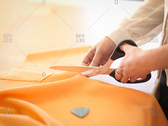 Fashion designer cutting cloth in fashion design studio, close up