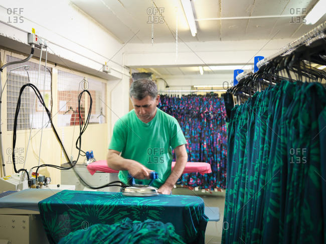 Garment worker ironing clothing in clothing factory
