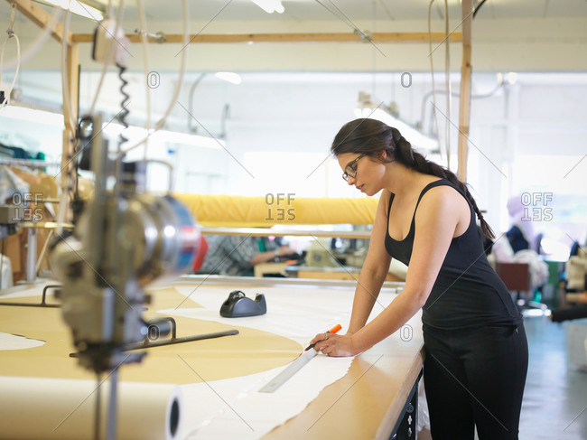 Female garment worker marking cloth in clothing factory