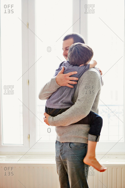 Father carrying son inside