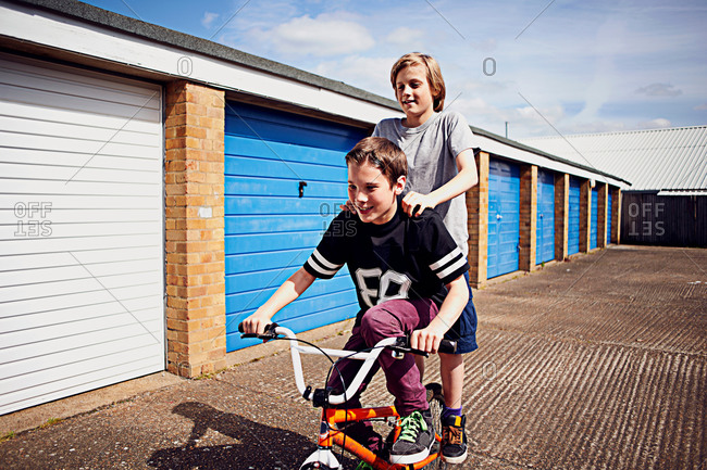 Boy giving friend a ride on bike passed garages