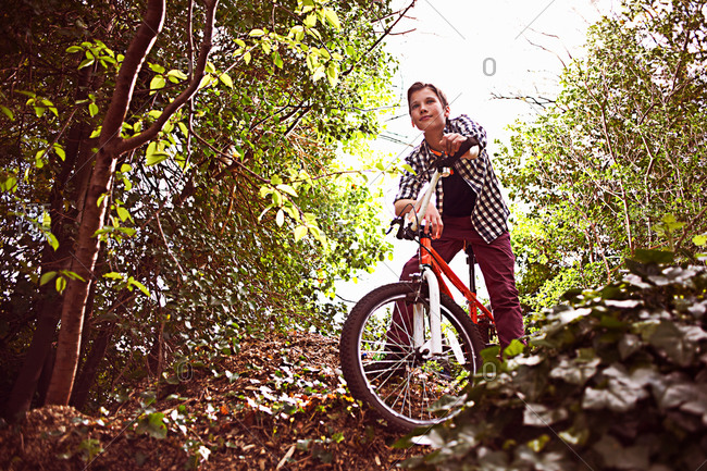 Boy cycling through forest - Offset