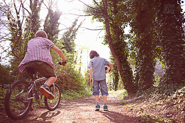 Rear view of a boy on bike with friend on forest path