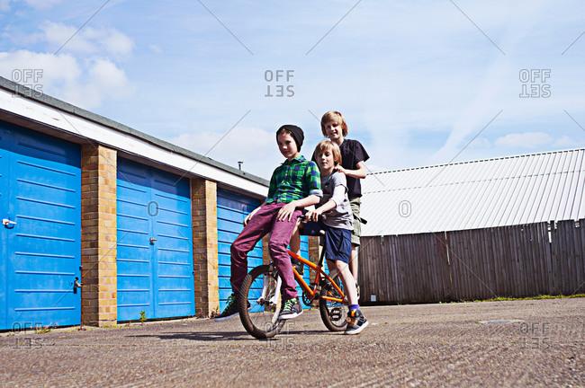 Boy giving friends a ride on bike pass garages