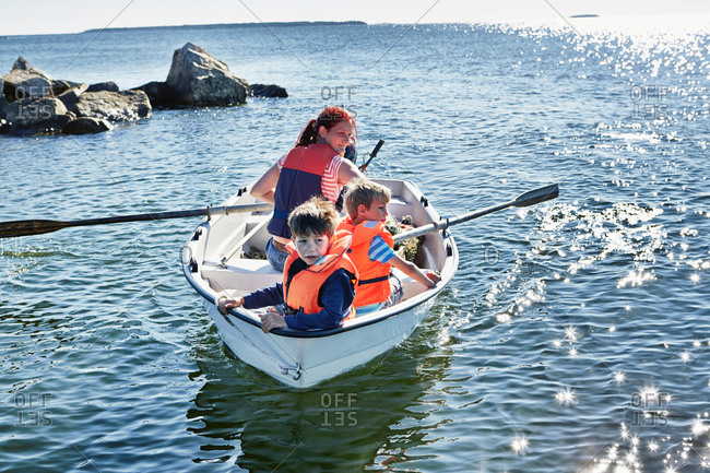 Mother and two young sons in rowing boat on lake, Gavle, Sweden