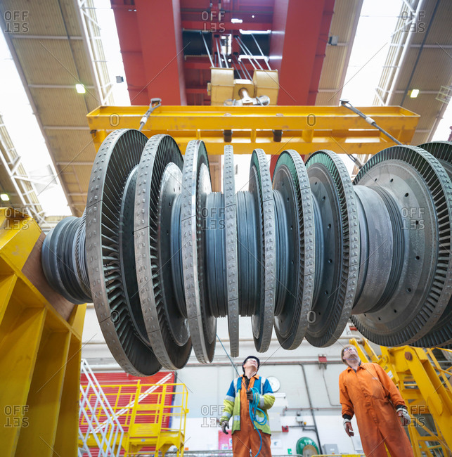 Banksman and crane operator lift turbine during power station outage, low angle view