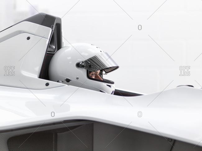 Test driver in crash helmet in supercar