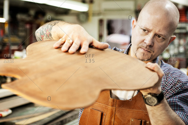 Guitar maker checking wooden guitar shape in workshop