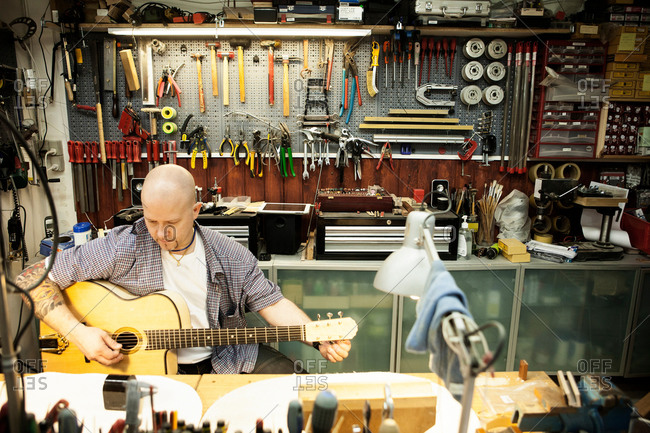 Guitar maker tuning acoustic guitar in workshop