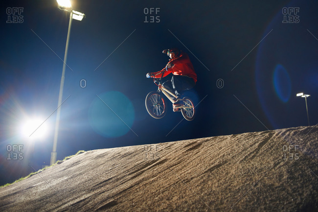 BMX-cyclist jumps his bike at night time