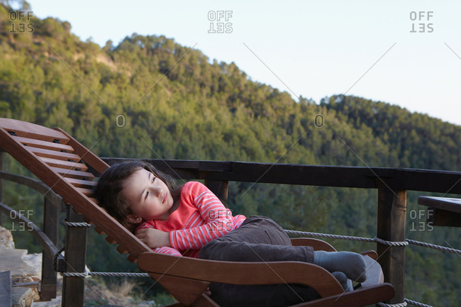 Young girl curled up on balcony deckchair gazing upward