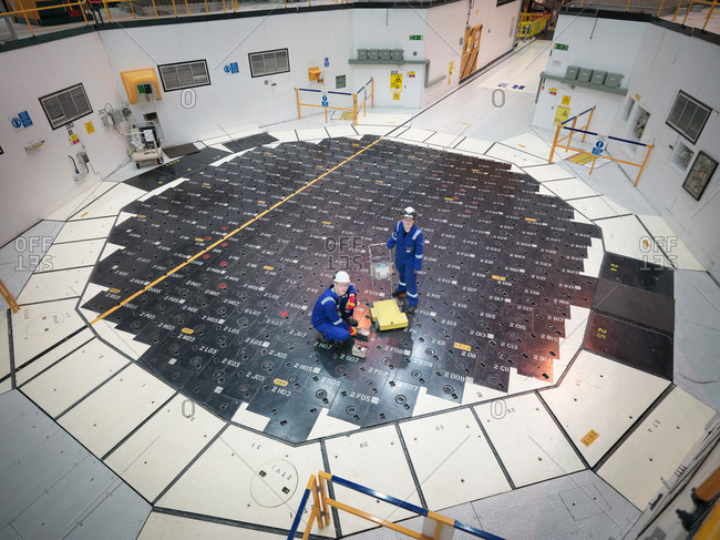 Engineers using sensors on pile cap in nuclear power station, high angle view