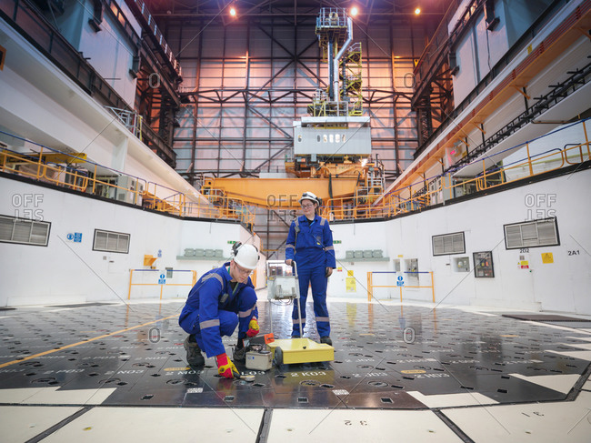 Engineers using sensors on pile cap in nuclear power station